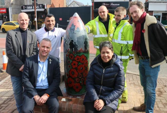 Stuart Henley (front left) with local traders celebrating the return of the artillery shell to Shell Corner last year.