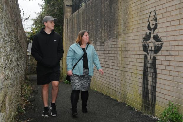 Ludlow residents Ruben Adams and Kate Adams admire the 'Monk' in Friar's Walk, Ludlow.