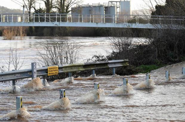Halesowen News: Rushing Storm Dennis floodwater gushes over Outfall Works Road in Hereford. Picture: Chris Moore