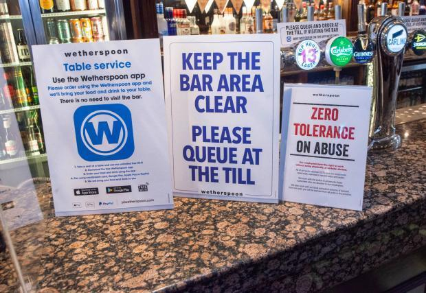 Social distancing signs at the bar at the Golden Cross in Bromsgrove. PIC: Martin Humby
