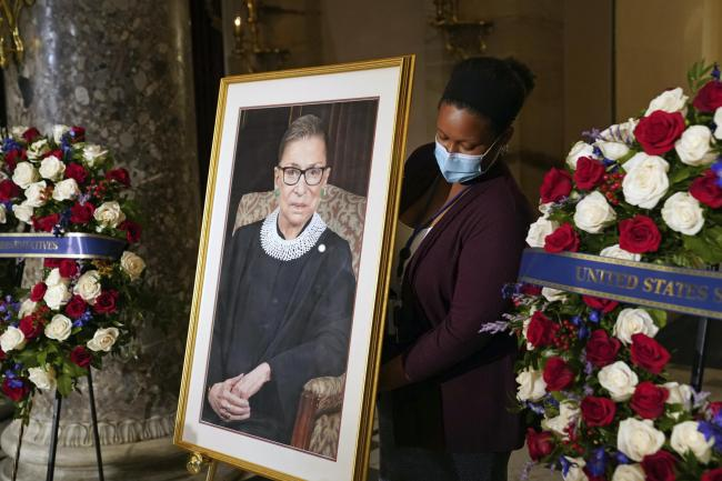 A staff member places a photo of Justice Ruth Bader Ginsburg before a ceremony for her to lie in state in Statuary Hall at the US Capitol
