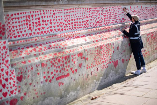 A volunteer adds hearts to the Covid-19 memorial wall in Westminster, central London