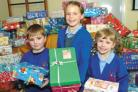 Newfield Park pupils (from left) Robert Bingley, aged four, Isabella Alderson, aged nine and four-year-old Poppy Parsons with the gift-filled shoeboxes. (To buy: 461002M)