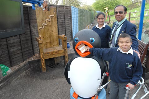 Meadows principal Gordon Phillips, pupils (left) Sharnjit Kaur, aged 13, and Kale Foster, aged 14, with one of the new litter bins and the carved chair in the Bluebell Wood Learning Centre.(To buy:81228M)