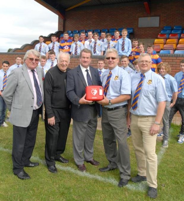 """Hearts"" of England representatives John Freestone (left) Alan Chapman and Stephen Ward present the defribulator to Old Halesonians junior section chairman John Wragg and U16s coach Paul Dando, flanked by young players. (To buy:391221M)"