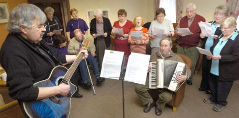 Pete James (left) leads staff and residents in the song. (To buy: 061304L)