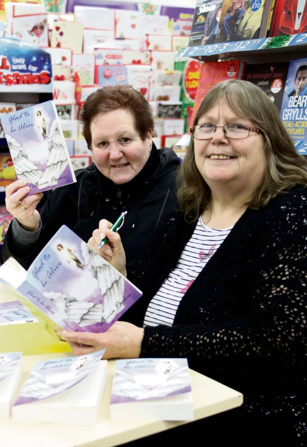 Halesowen News: Patricia Parkes (right) signs a copy of her book for Audrey Potter. (Buy photo: 1318AM)