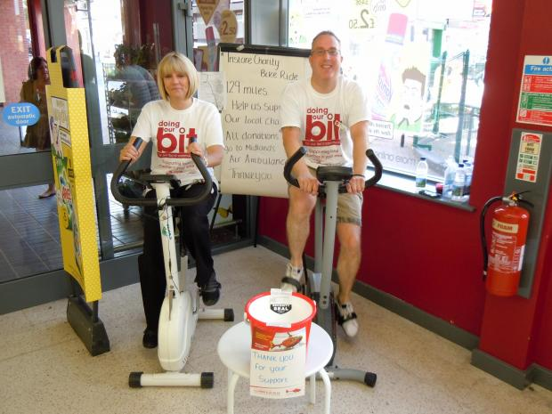 Wilko staff Janette Cartridge and manager Neil Fisher. pedalling for charity.