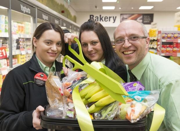 Halesowen Co-op manager Gemma Brayne (centre) cuts the ribbon to celebrate the opening of the new store with colleagues Kirsty Behan and Carl Smitheman.