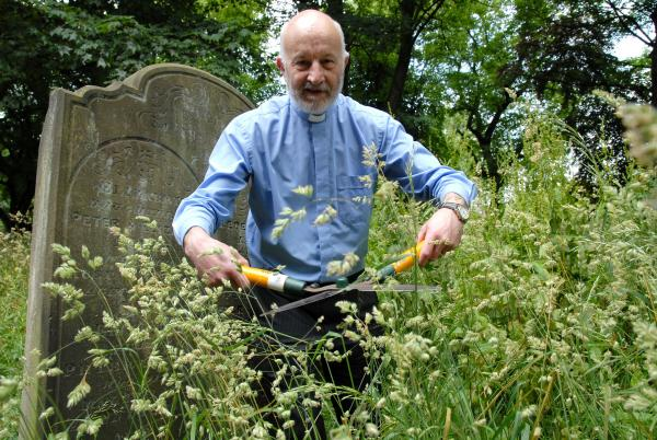 Rev Ian Shelton in the overgrown churchyard at St Giles Church, Rowley Regis.
