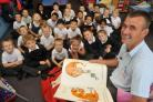 Postie Mike Billingham with year two pupils.