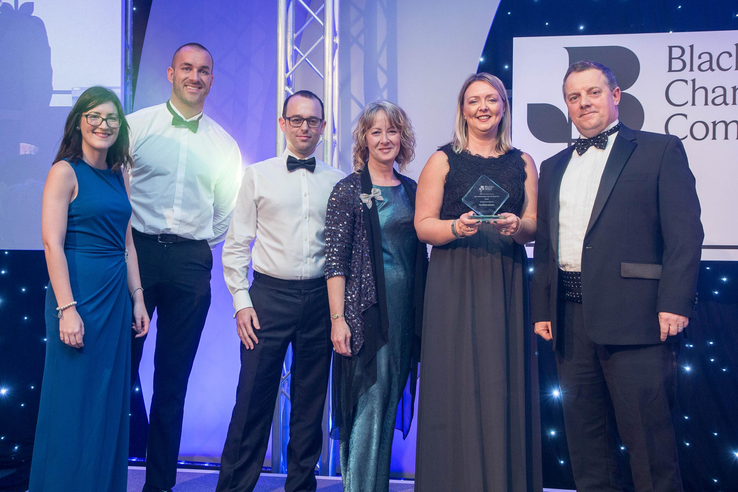 Thursfields Solicitors' Kirsty Underhill, Tim Edwards, Gareth Burge, Jane Rudge and Julia Warrilow pick up their Black Country Chamber of Commerce award from James Thomas-Horton. Photo: Codsall Photographic