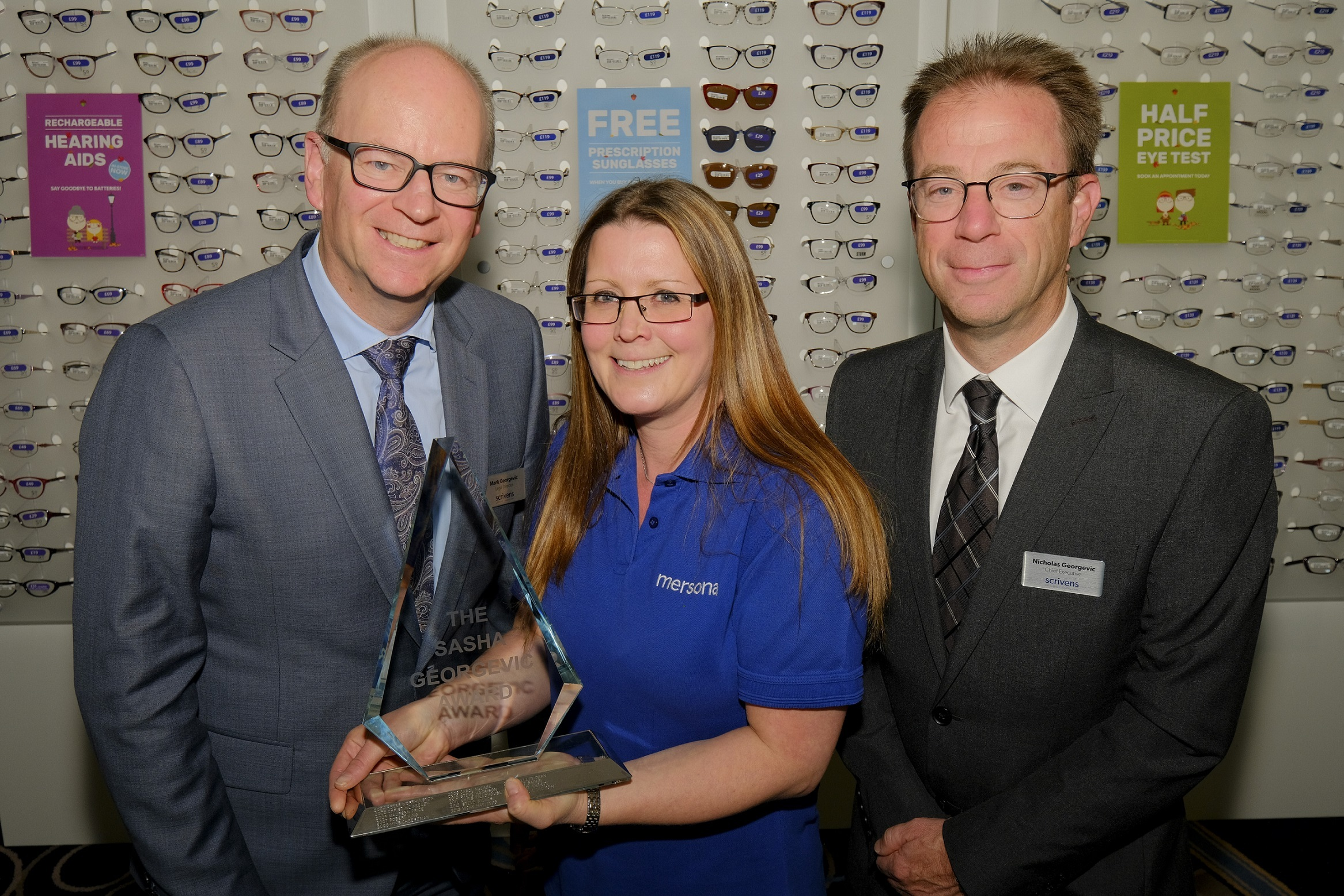 Award winner Angela Melrose, with Scrivens Opticians' Mark and Nicholas Georgevic.