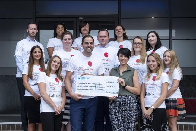Callum Haynes, Talbots Law director, joins staff to presents a cheque to Kirsty White, of Birmingham Children's Hospital Charity.