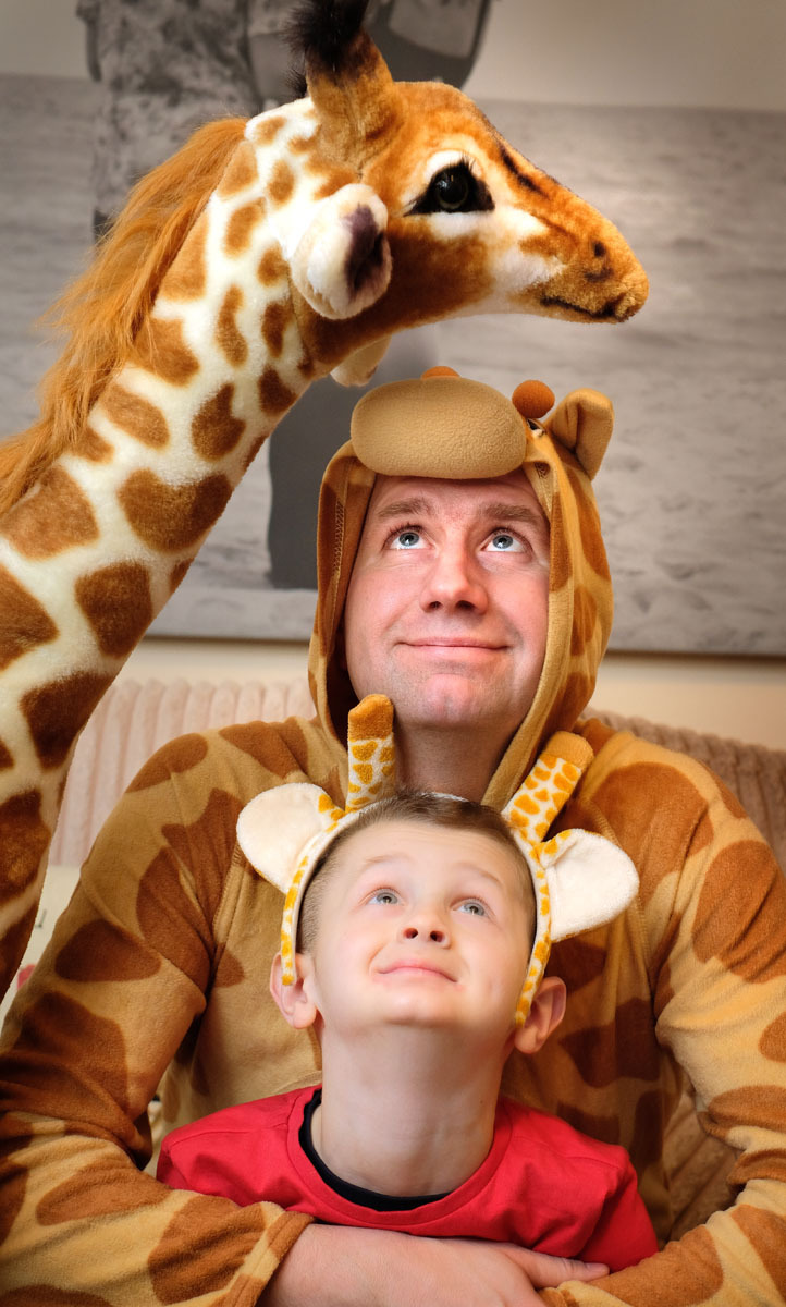 Stuart Atkiss with his six-year-old son Taylor and Pumpkin Pie the giraffe.