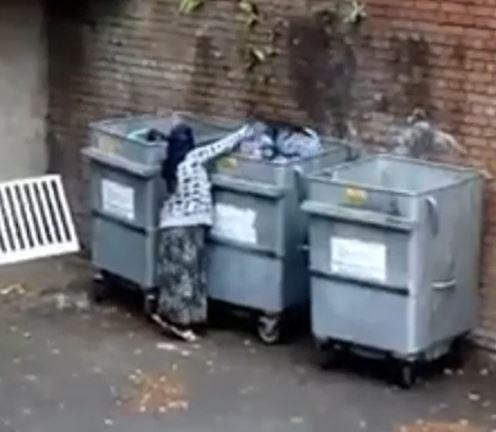 A still image from the video showing a woman rifling through bins in Lye
